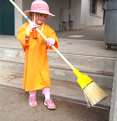 Little girl sweeping on community service day